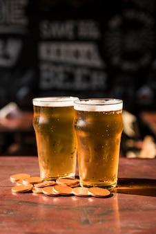 Glazen drankje in de buurt van hoop munten aan tafel