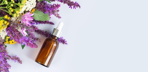 Glazen druppelaar bruine fles met bloemen, natuurlijke biologische huidverzorging cosmetica