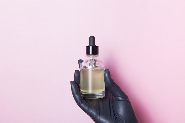 Glazen druppelflesje in een zwarte medische vrouwelijke hand op een roze oppervlak