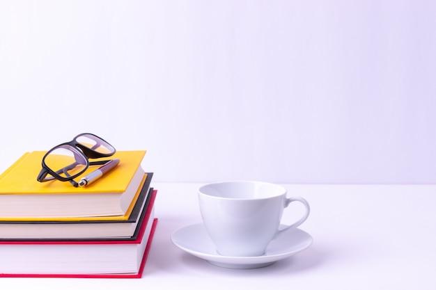 Glazen en boeken op witte tafel