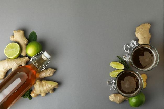 Glazen en een fles gemberbier en ingrediënten op grijs