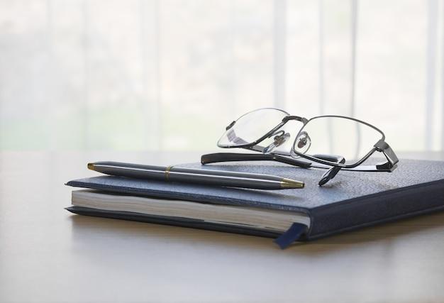 Glazen en pen op een boek
