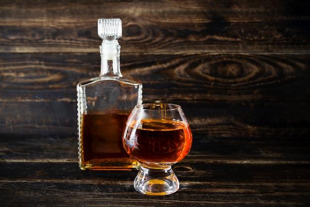 Glazen flacon en wijnglas met cognac op houten plankoppervlak.