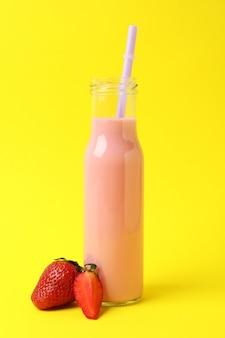 Glazen fles aardbeienmilkshake op gele achtergrond
