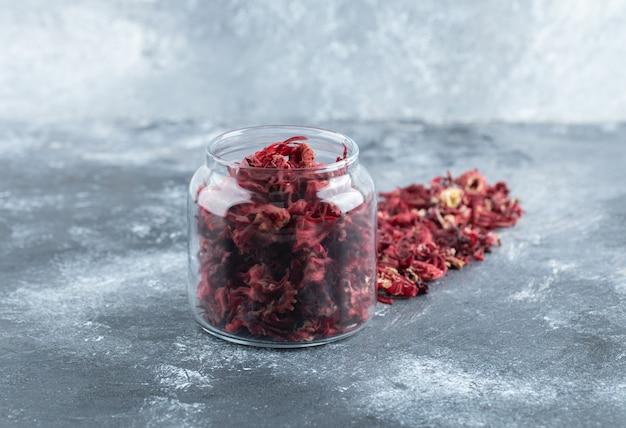 Glazen fles gedroogde bloemblaadjes op marmeren tafel.