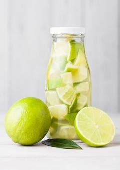 Glazen fles limoen nog fruitwater met fruit