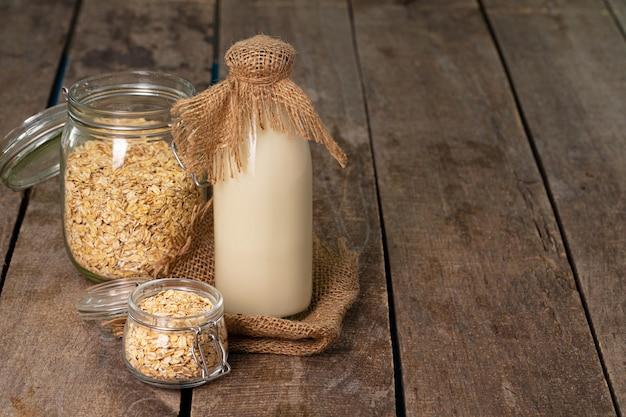 Glazen fles melk en havervlokken in pot op oude houten tafel