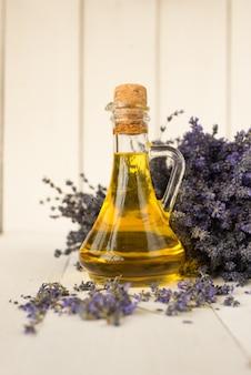 Glazen fles met aroma-olie en een boeket verse provençaalse lavendelbloemen.