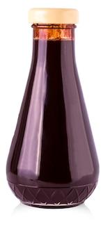 Glazen fles met donkere saus op een witte achtergrond.