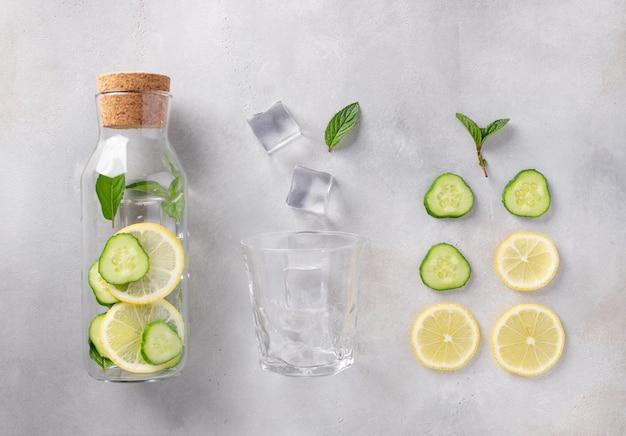 Glazen fles met doordrenkt water met citroen, komkommer, munt
