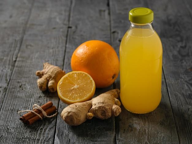 Glazen fles met een drankje van gemberwortel, citroen, sinaasappel, honing en kaneel op een tafel.
