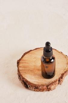 Glazen fles met een pipet op een zaagsnede van een boom op een beige getextureerde achtergrondkopieerruimte