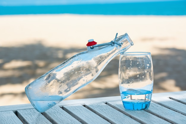 Glazen fles met glas op tafel met uitzicht op de zanderige kust.