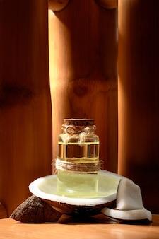 Glazen fles met kokosolie met verse kokos op een natuurlijke houten achtergrond. spa.