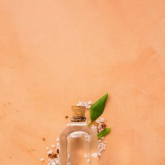 Glazen fles op oranje achtergrond met kopie ruimte