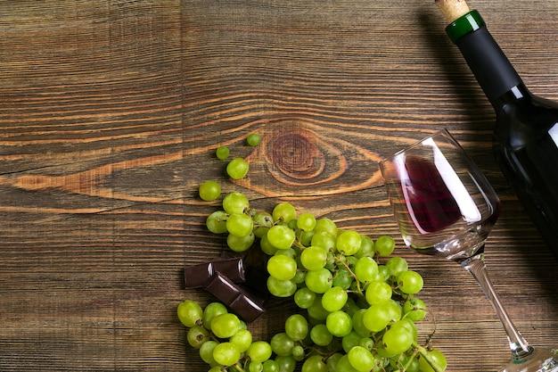 Glazen fles rode wijn en druif op een houten tafel