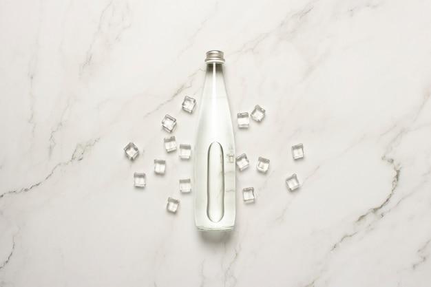 Glazen fles water en ijsblokjes op een marmeren tafel.