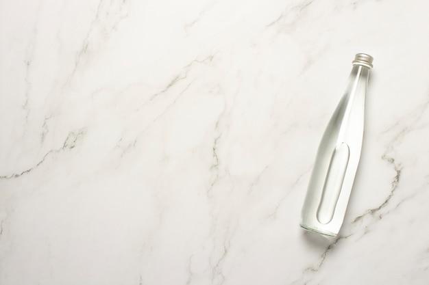 Glazen fles water op een marmeren tafel. het concept van warmte, waterbalans, voeding, gewichtsverlies, verfrissende drankjes. plat lag, bovenaanzicht