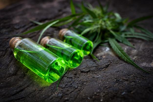 Glazen flesje met cbd-olie en cannabisbloesem op de achtergrond
