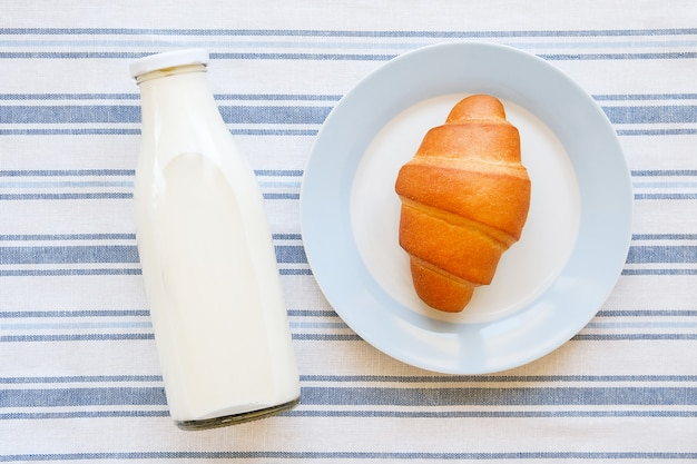 Glazen flesje met melk en bakkerijproducten op een croissantplaat