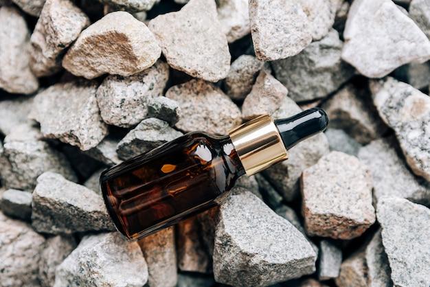Glazen flesje met pipet op granieten steentjes