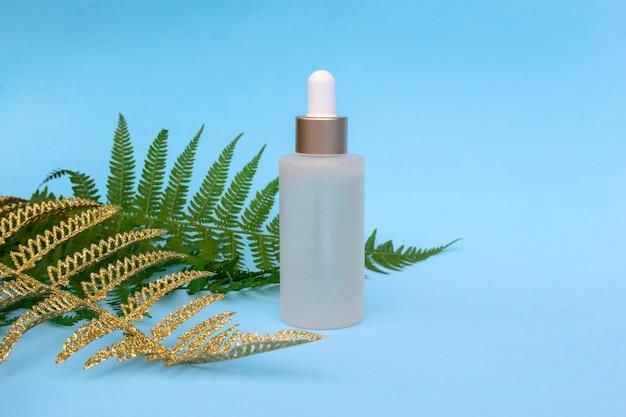 Glazen flesje natuurlijke olie met gouden varens palmbladeren. cosmetische huidverzorgingsproducten, modern concept van organische schoonheidstrend.
