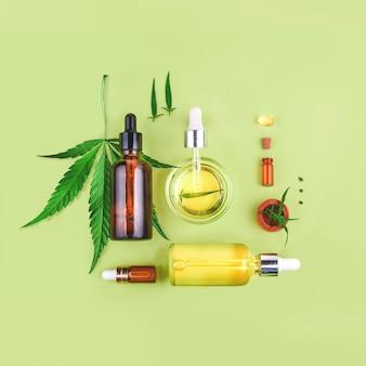 Glazen flesjes met cbd-olie, thc-tinctuur en hennepbladeren op groen
