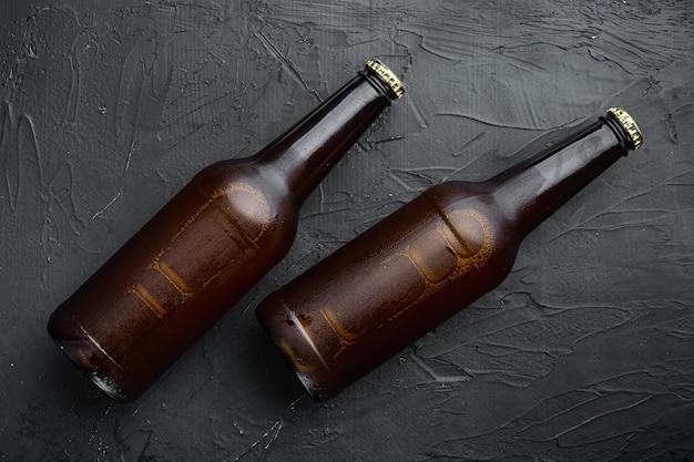 Glazen flessen bier set, op zwarte stenen tafel, bovenaanzicht plat lag