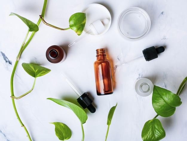 Glazen flessen en pot voor natuurlijke cosmetica op een witte marmeren achtergrond