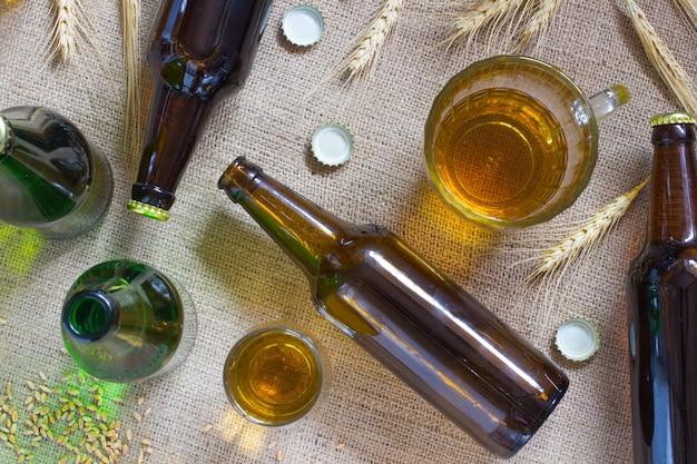 Glazen flessen. glazen mok en een glas bier. aartjes van tarwe