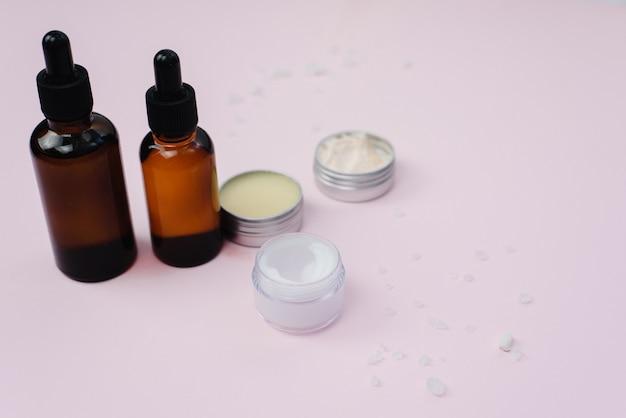 Glazen flessen met hydraterende serum, potjes crème en balsem op een roze pastel achtergrond. zelfgemaakte huidverzorging. copyspace, sjabloon