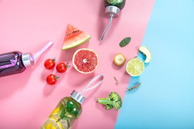 Glazen flessen met natuurlijke dranken op een gekleurde muur