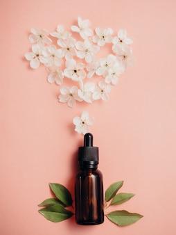 Glazen flessen met olie, parfum op een roze oppervlak met bloeiende kersen. platliggend, minimalisme.
