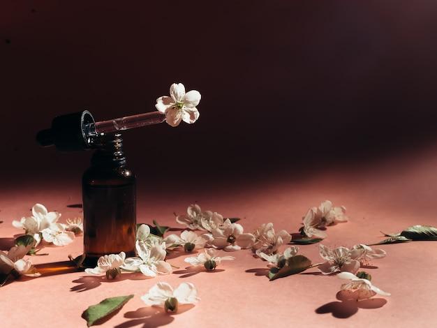 Glazen flessen met olie, parfum. spa. cosmetica. bloeiende kers.