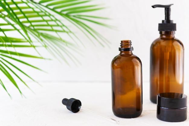 Glazen flessen voor cosmetica en oliën met palmtakken op een witte achtergrond