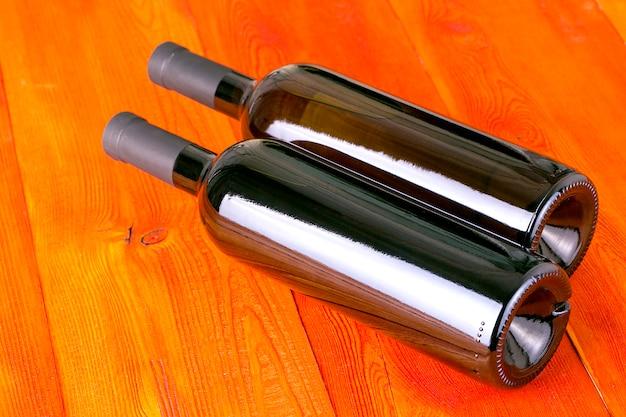 Glazen flessen wijn op rode houten tafel.