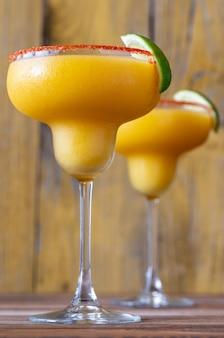 Glazen frozen mango margarita-cocktails gegarneerd met paprika-zoutrand