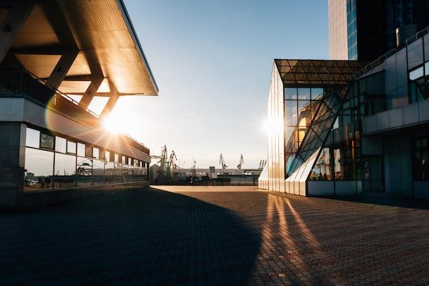 Glazen gebouwen in de avond zonlicht tegen de achtergrond van de zeehaven