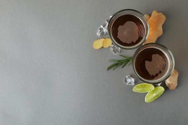 Glazen gemberbier en ingrediënten op grijs