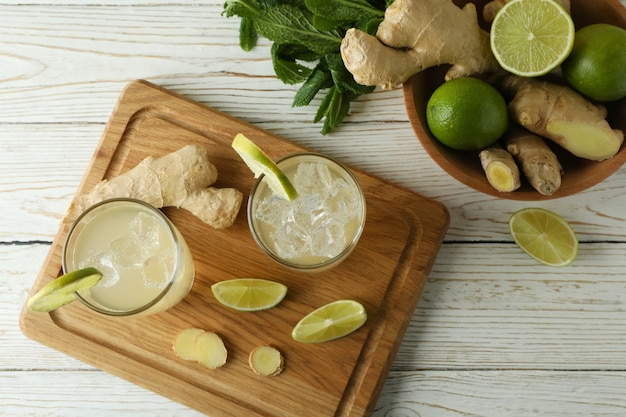 Glazen gemberbier en ingrediënten op witte houten lijst