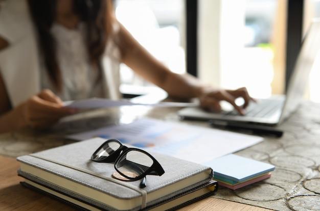 Glazen geplaatst op notebooks, achtergrond wazig mensen zitten met behulp van laptop.