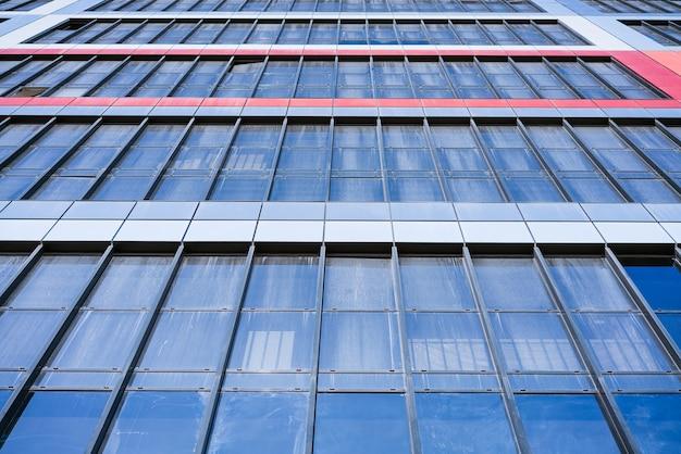 Glazen gevel van een huis tegen een blauwe lucht onderaanzicht