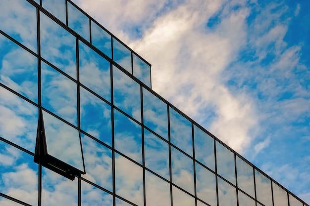 Glazen gevel van een zakencentrum tegen een blauwe hemel met wolken