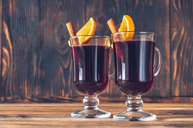 Glazen glühwein gegarneerd met kaneel en sinaasappel