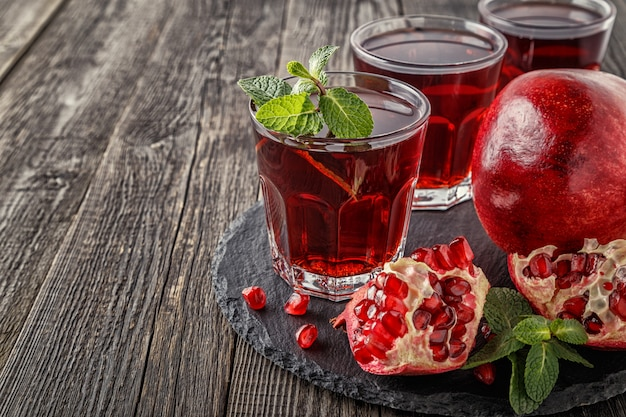 Glazen granaatappelsap met vers granaatappelfruit en munt, gezond drankconcept