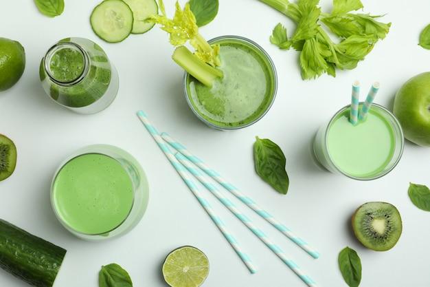 Glazen groene smoothie en ingrediënten op witte achtergrond, bovenaanzicht