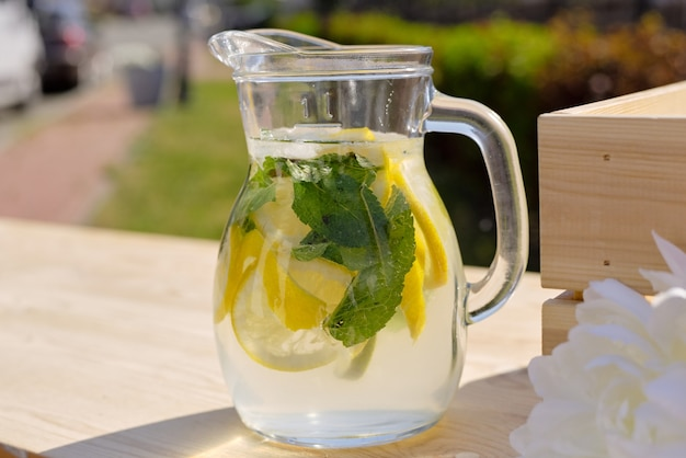 Glazen kan met verse koele zelfgemaakte limonade staande op houten marktkraam op zonnige dag in natuurlijke omgeving