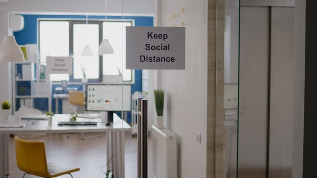 Glazen kantoor met poster voor sociale afstand erop, moderne kantoortrappen tijdens covid 19 coronavirus pandemie, wereldwijde economische crisis.