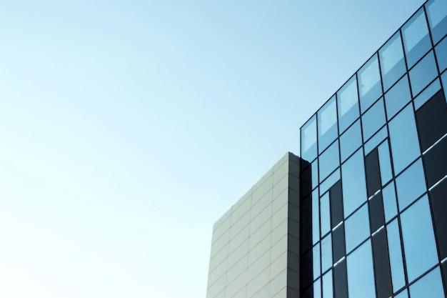 Glazen kantoorgebouw, zicht op de lucht weerspiegeld in de ramen.
