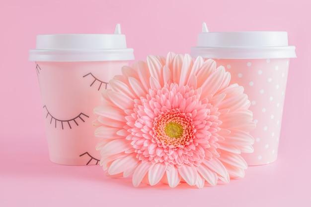 Glazen koffie take-away en gerbera bloem op roze pastel achtergrond.